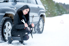 Fault car in the winter. Young beautiful girl trying to repair t Stock Photos
