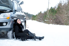 Fault car in the winter. Young beautiful girl trying to repair t Stock Photography