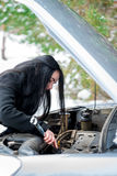 Fault car in the winter. Young beautiful girl trying to repair t. He car, engine repair, tire change Royalty Free Stock Photo