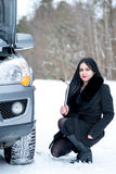 Fault car in the winter. Young beautiful girl trying to repair t. He car, engine repair, tire change Royalty Free Stock Image