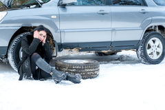 Fault car in the winter. Young beautiful girl trying to repair t. He car, engine repair, tire change Royalty Free Stock Photography