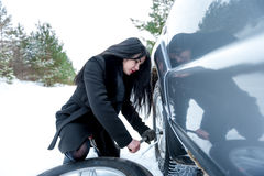 Fault car in the winter. Young beautiful girl trying to repair t. He car, engine repair, tire change Stock Photos