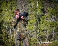 Fauna, fotógrafo del hombre de la naturaleza en el tiroteo del equipo del camuflaje, tomando imágenes Imágenes de archivo libres de regalías