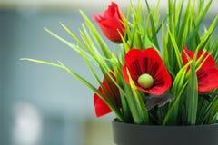 Fausses fleurs dans le pot noir photographie stock libre de droits