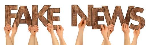 FAUSSES personnes d'ACTUALITÉS supportant l'isolant en bois de lettres de chêne rustique brun photo libre de droits