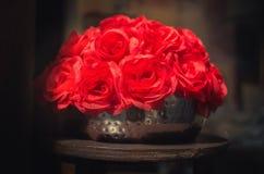 Fausses roses rouges dans les ombres sur un pot métallique - le jour de valentine Images stock