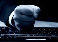 Faust auf Tastatur lizenzfreie stockbilder