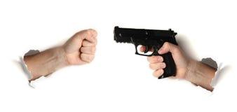 Faust gegen Hand mit Gewehr-, Gefahren- und Gewalttätigkeitskonzept lizenzfreies stockbild