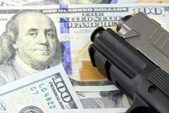 Faustfeuerwaffe mit amerikanischer Währung Stockbild
