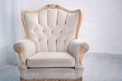 Fauteuil en bois en cuir beige avec le décor d'or dans un salon blanc photos stock