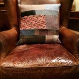 Fauteuil en cuir avec le coussin décoratif photographie stock libre de droits