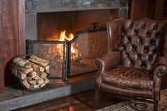 Fauteuil et cheminée en cuir Photographie stock libre de droits