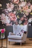 Fauteuil gris avec le coussin se tenant en vraie photo d'intérieur foncé de salon avec la lampe de papier peint floral et d'or photos stock