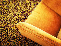 Fauteuil orange de velours sur le tapis de léopard Photo libre de droits