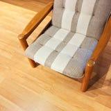 Fauteuil rayé confortable sur un plancher en bois Images libres de droits