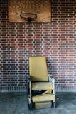 Fauteuil roulant étendu jaune de vintage sous le cercle de basket-ball - hôpital abandonné Images stock