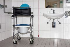 Fauteuil roulant avec la casserole incluse de toilette dans la maison de retraite Photographie stock libre de droits