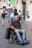 Fauteuil roulant de petit morceau d'homme et assistant d'homme de couleur Photos libres de droits