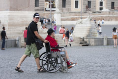 Fauteuil roulant et assistant de petit morceau d'homme Photo libre de droits