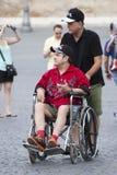 Fauteuil roulant et assistant de petit morceau d'homme Photographie stock