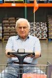 Fauteuil roulant motorisé de vieux entraînements d'homme Photographie stock libre de droits