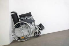 fauteuil roulant plié à un mur blanc photos stock