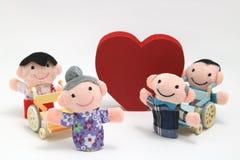 Fauteuil roulant, un grand coeur rouge, et deux-familles sur le fond blanc Photos libres de droits