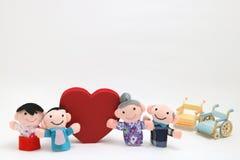Fauteuil roulant, un grand coeur rouge, et deux-familles sur le fond blanc Images stock