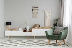 Fauteuil vert sur le tapis modelé dans l'interio lumineux de salon images libres de droits