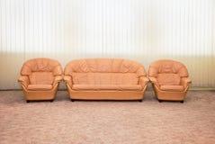Fauteuils et sofa en cuir dans l'intérieur de la pièce Photographie stock libre de droits