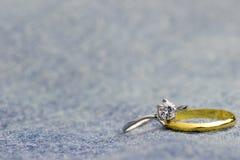 Faux anneau de bague à diamant et d'or placé sur le jecket de Jean photographie stock