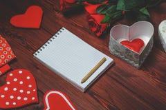 Faux bloc-notes haut ouvert, coeurs de jouet et roses rouges sur la table en bois romantique Photographie stock libre de droits