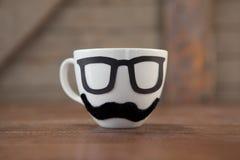 Faux moustache et lunettes sur la tasse Photographie stock libre de droits