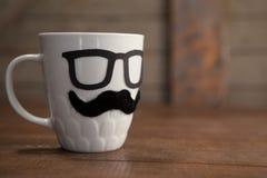Faux moustache et lunettes sur la tasse Image libre de droits