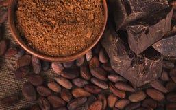 Fave di cacao crude, ciotola dell'argilla con cacao in polvere, cioccolato sul sacco immagine stock