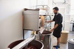 Fave di cacao di torrefazione del lavoratore mentre lavorando in una fabbrica del cioccolato fotografie stock