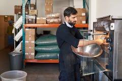 Fave di cacao di torrefazione del lavoratore in una fabbrica artigianale di fabbricazione di cioccolato fotografie stock libere da diritti