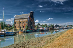 Faversham river front. The Faversham docks with several boats and a warehouse Stock Image