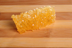 Favo con miele su un tagliere di legno Fotografie Stock