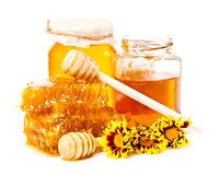 Favo e barattoli dolci di miele con il bastone ed i fiori Immagini Stock