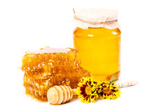 Favo e barattolo dolci di miele con il bastone ed i fiori Fotografia Stock Libera da Diritti