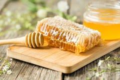 Favo sul bordo di legno con il cucchiaio del miele Fotografia Stock Libera da Diritti