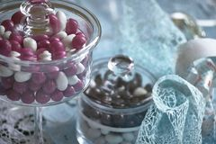 The favor for baptism. Beautiful still life composed of a container of colored candies and blue ribbons used as a wedding favor for the feast of a Catholic royalty free stock images