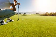 Favorable jugador de golf que apunta el tiro con el club en curso Fotografía de archivo libre de regalías