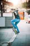 Favorable patinador que hace trucos y saltos en la calle Pase gratis Imagen de archivo libre de regalías