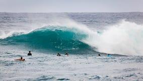Favorable playa Hawaii de la puesta del sol de las personas que practica surf Foto de archivo