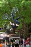 Favorable truco de Rider Goes Upside Down Performing BMX en la competencia Fotos de archivo libres de regalías