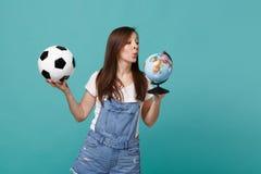 Favorit- lag för nyfiken ung flickafotbollsfanservice med fotbollbollen, jordvärldsjordklot som isoleras på blå turkos fotografering för bildbyråer