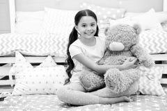 Favorit- leksak Flickabarnet sitter på björn för sängkramnalle i hennes sovrum Ungen förbereder sig att gå att bädda ned Angenäm  royaltyfri fotografi