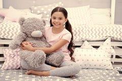 Favorit- leksak Flickabarnet sitter på björn för sängkramnalle i hennes sovrum Ungen förbereder sig att gå att bädda ned Angenäm  royaltyfri bild
